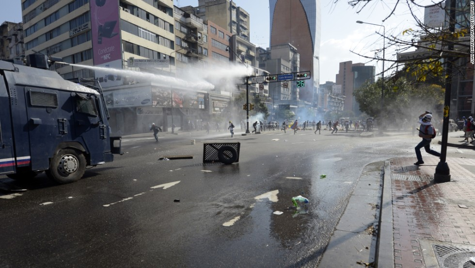 Law enforcement personnel use water cannons to disperse demonstrators on March 22.
