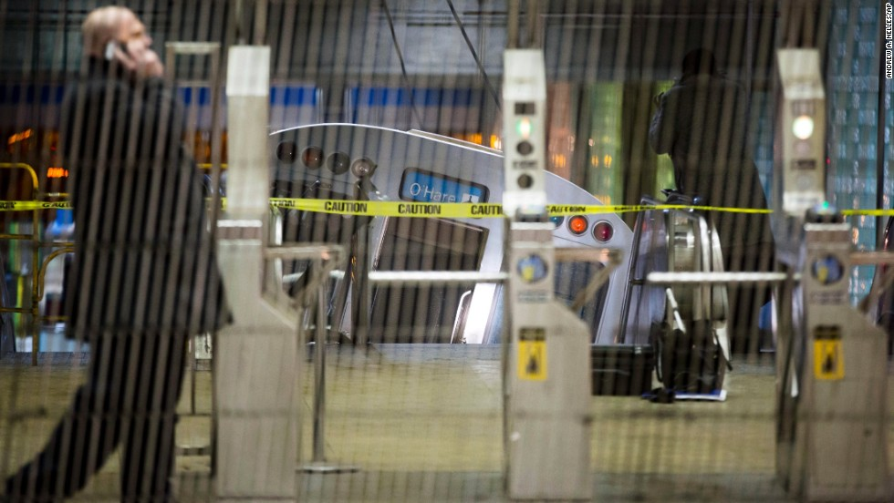 A derailed train car rests on an escalator at the O'Hare station.