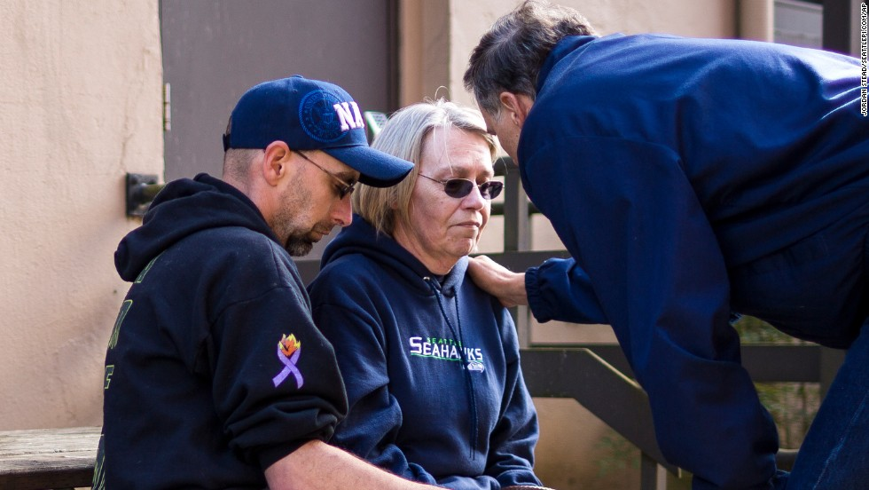 Gov. Jay Inslee, right, comforts Barbara Welsh after a news conference March 23 outside the Arlington Police Department. Welsh's husband, Bill, was among the scores of people listed as missing immediately after the disaster.