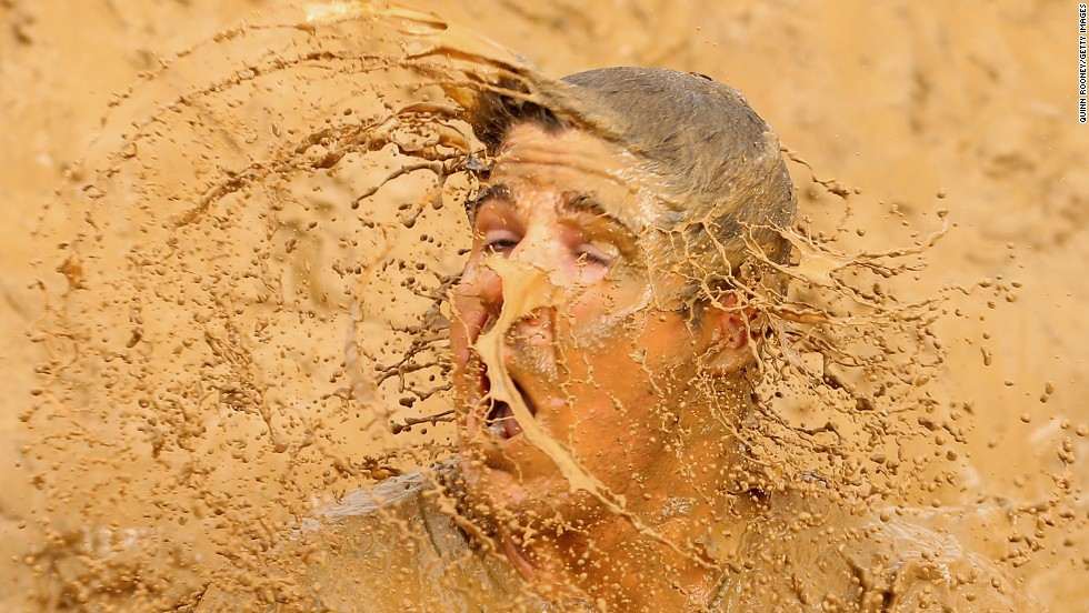 A competitor falls into muddy water during the Tough Mudder obstacle race held Saturday, March 22, in Phillip Island, Australia.