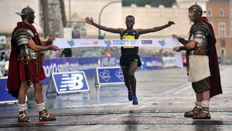 Two men dressed as centurions hold the finish line banner as Shume Hailu Legese wins the Rome Marathon on Sunday, March 23.