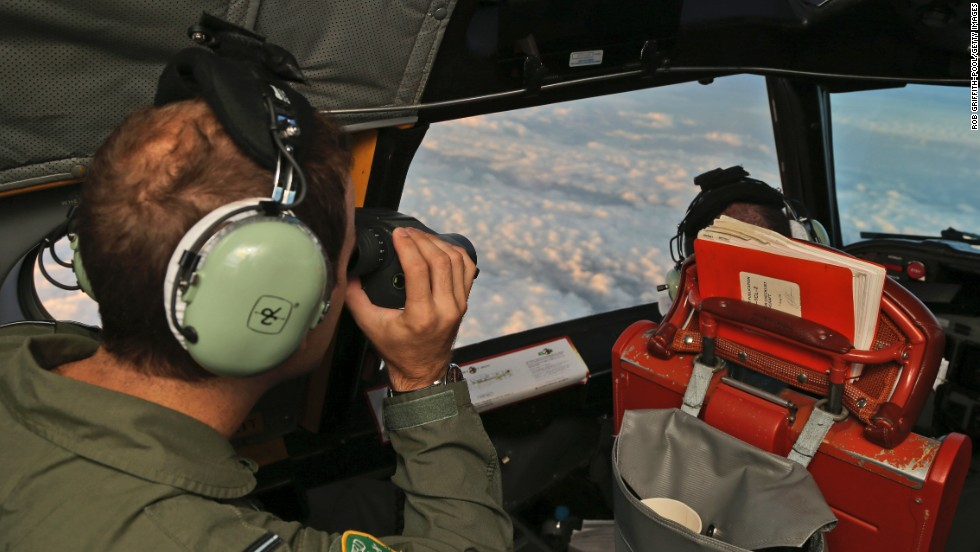 "Crew aboard an Australian P-3 Orion ""sub hunter"" scan the southern Indian Ocean as they search for the missing plane on March 23."