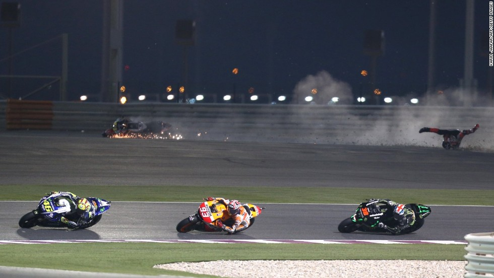 MotoGP riders negotiate a turn while a fellow competitor crashes behind them during the Qatar Grand Prix on Sunday, March 23, in Doha, Qatar.