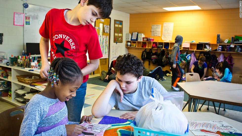Max Bradley, 13, right, helps Carrington Stallworth, 7, with her reading while Ian Ferreira, 11, looks on. At Hess Academy, it's common to see some students working at desks while others are sprawled on the floor.