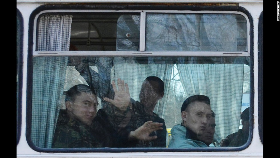 Ukrainian marines wave as they leave a base in Feodosia, Crimea, on Tuesday, March 25.