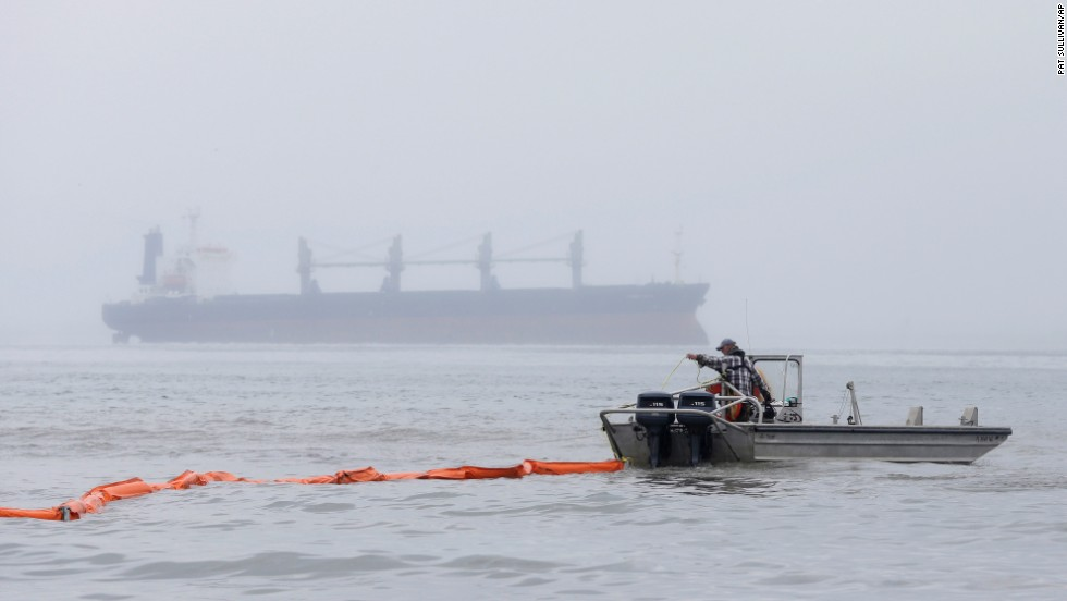 A boat drags an oil boom out into the water along East Beach on March 24.