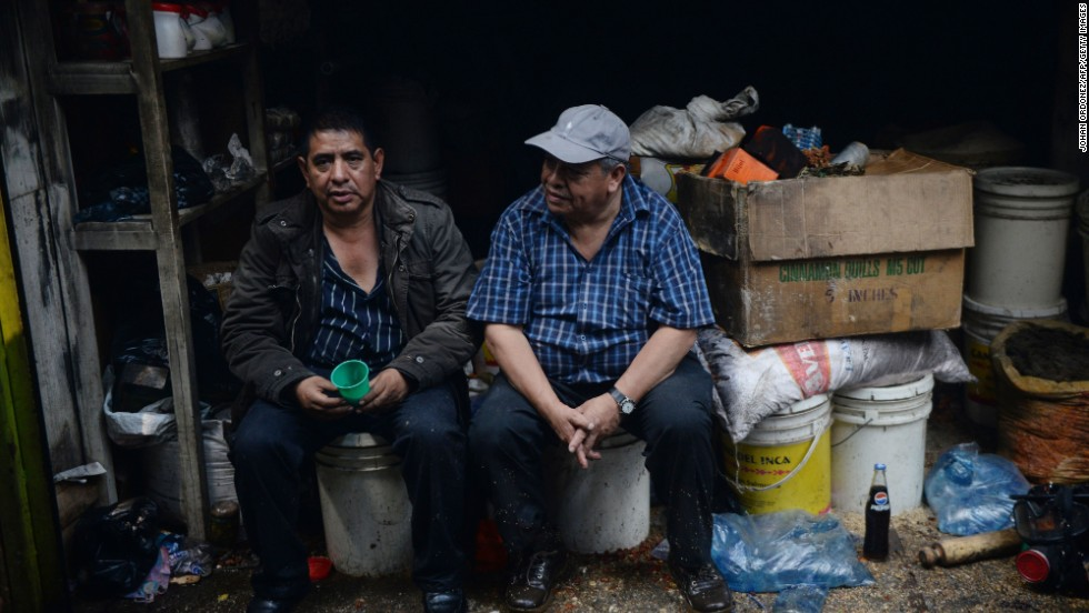 Two shopkeepers sit by their stalls after a fire Tuesday, March 25, at La Terminal market in Guatemala City. The fire destroyed approximately 6,000 stalls in the market, the state-run AGN news agency reported.