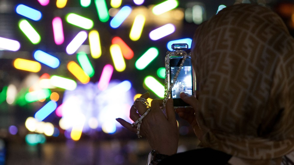 A spectator takes a photo of Big Tree, a light installation by architect Jacques Rival.