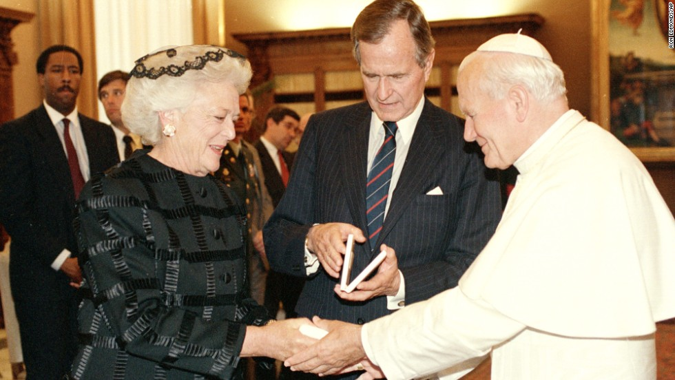 Pope John Paul II presents first lady Barbara Bush with a Vatican Medal as President George H.W. Bush looks at his medal during a ceremony at the Vatican in 1989.