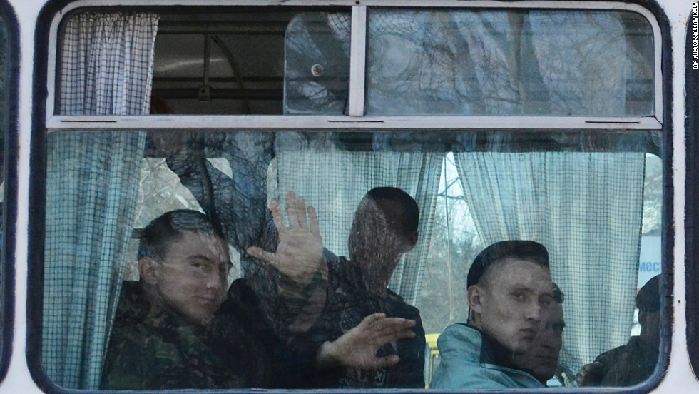 FEODOSIA, CRIMEA: Ukrainian marines leave their base in Crimean Feodosia. Ukrainian soldiers piled onto buses and began their journey to mainland Ukraine, as former comrades saluted them from outside a base overrun by Russian forces in the past few days.