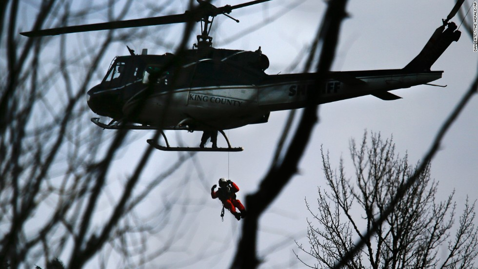 A King County Sheriff's Office helicopter lowers a rescue worker on March 24.