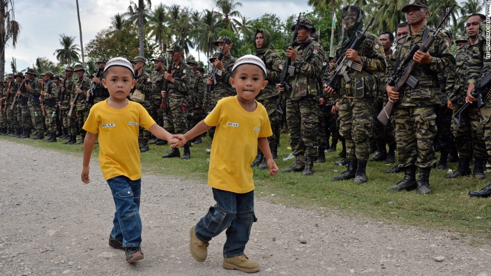 MARCH 27 - SULTAN KUDARAT, PHILIPPINES: Two boys walk past Moro Islamic Liberation Front rebels during a rally in support of the peace agreement on the southern Philippine island of Mindanao. The biggest Muslim rebel group in the country signed the historic pact, ending one of Asia's longest and deadliest conflicts.