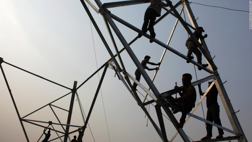 Laborers work without safety equipment as they install electricity poles in Dhaka, Bangladesh, on Friday, March 21.