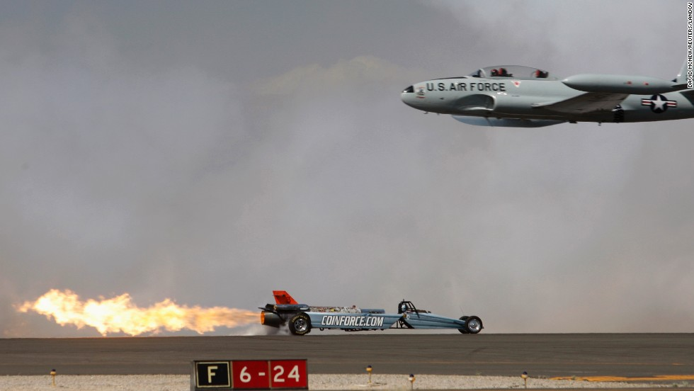 A Lockheed T-33 Shooting Star flies past the Smoke-N-Thunder jet car during a race between the two at the Los Angeles County Air Show on Friday, March 21.