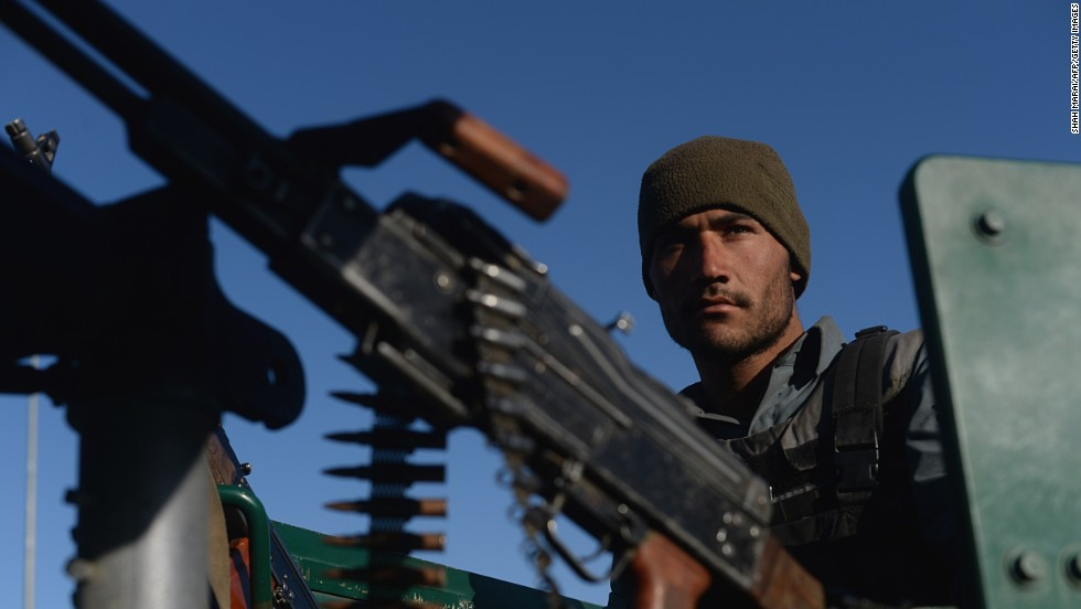 "An Afghan policeman is seen behind a machine gun Tuesday, March 25, after <a href=""http://www.cnn.com/2014/03/25/world/asia/afghanistan-violence/index.html"">a deadly attack</a> on an election office in Kabul."