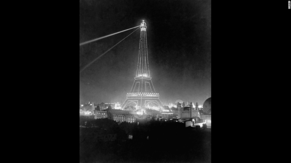 Spotlights illuminate the Eiffel Tower during the 1900 Universal Exposition.