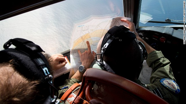 Flight Lieutenant Jayson Nichols looks at a map as he flies aboard a Royal Australian Air Force AP-3C Orion aircraft searching for missing Malaysian Airlines flight MH370 over the southern Indian Ocean on March 27, 2014 off the coast of Perth, Australia