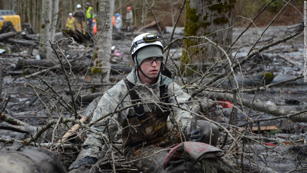 Staff Sgt. Jonathon Hernas of the Air National Guard carefully makes his way across debris and mud while searching for missing people March 29 in Oso.