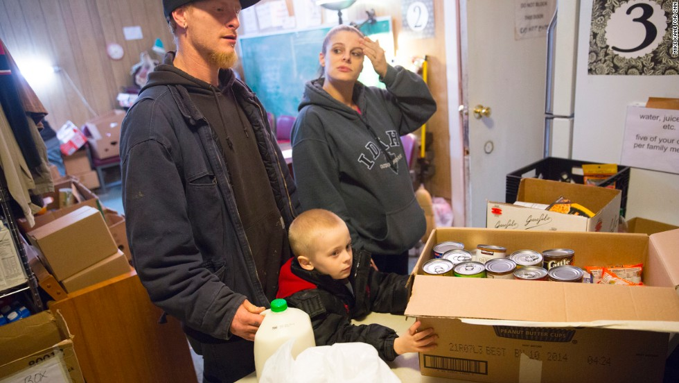 C.J. and Michelle Anderson, along with their 4-year-old son Cameron, pick up food from the Darrington Food Bank on Friday, March 28, at the First Baptist Church in Darrington. C.J.'s commute to the chicken farm where he works has gone from three minutes to three hours because of the closure of State Route 530, cutting down time with family and hurting them financially with increased fuel costs.