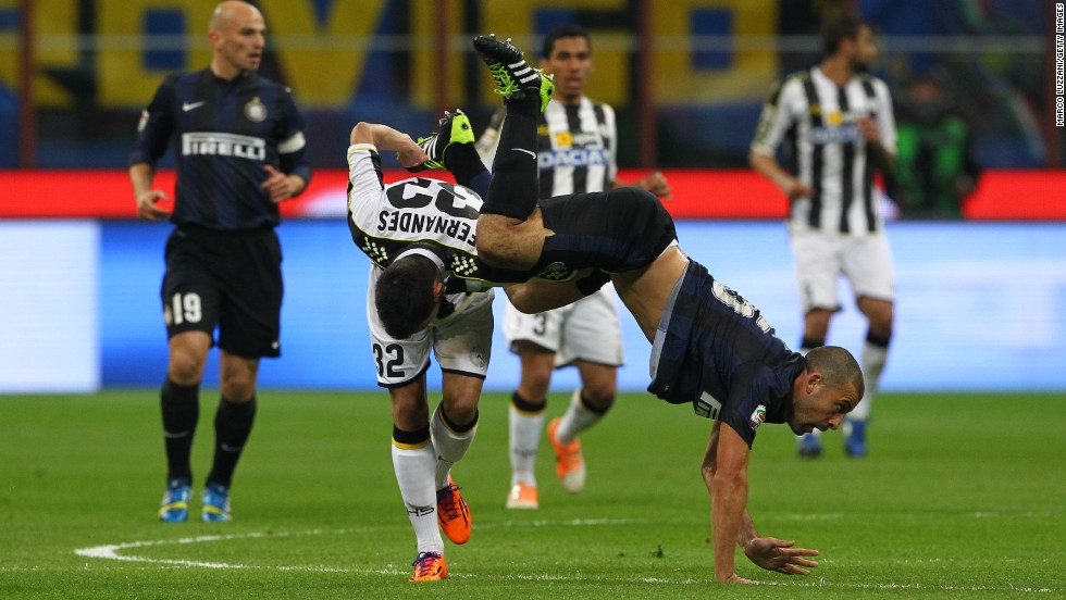 Inter's Walter Samuel falls over Udinese's Bruno Fernandes during a Serie A soccer match Thursday, March 27, in Milan, Italy.