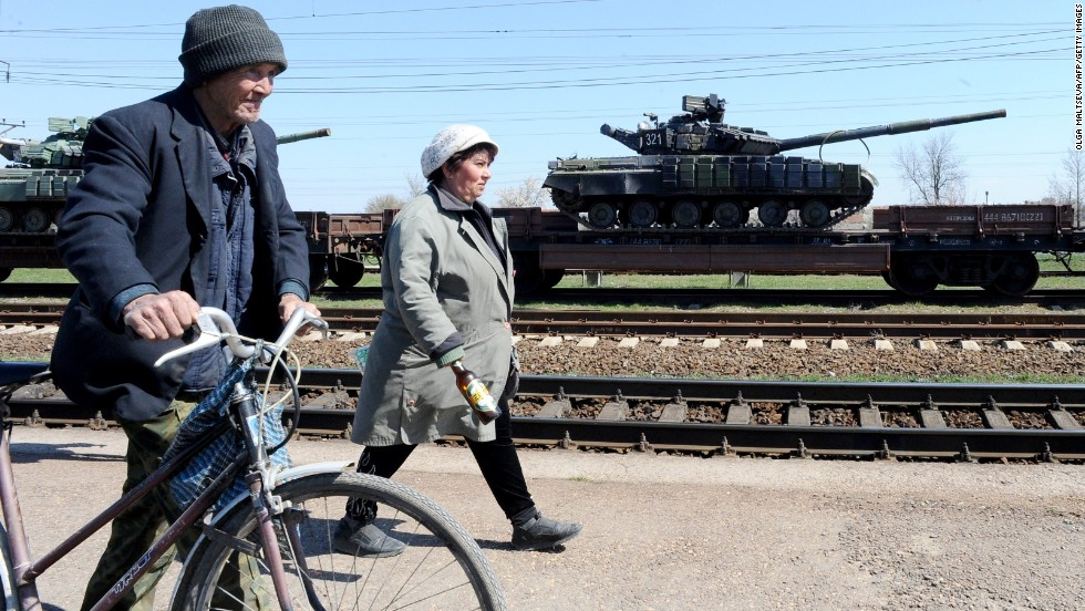 People walk past a train loaded with Russian tanks Monday, March 31, in the Gvardeyskoe railway station near Simferopol, Crimea.