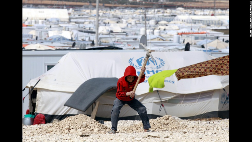 A boy uses a tool to dig a hole at the Zaatari refugee camp in northern Jordan on Saturday, March 15.