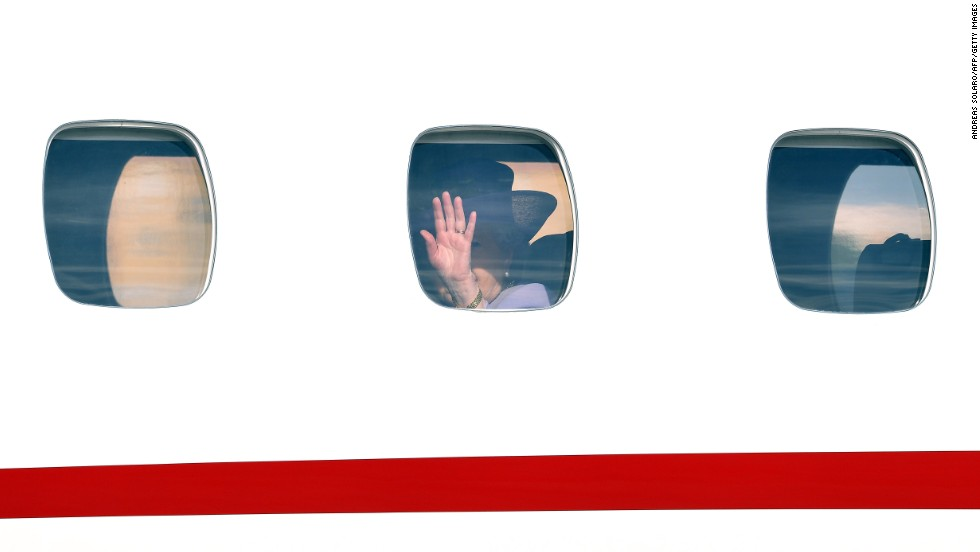 The Queen waves goodbye through an airplane window at Ciampino airport.