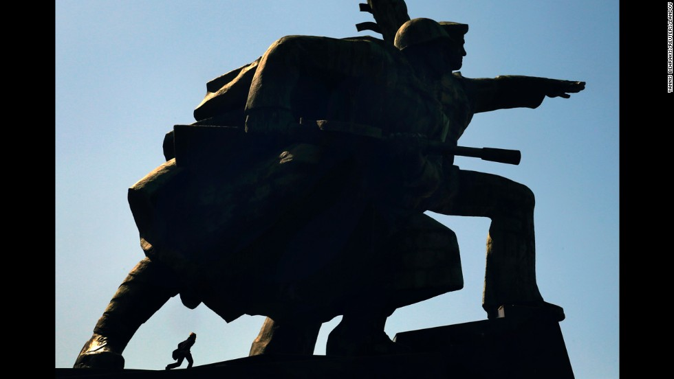 "A local walks by the ""Soldier and Sailor"" memorial in Sevastopol, Crimea, on Sunday, March 30. The sculpture is 131 feet tall."