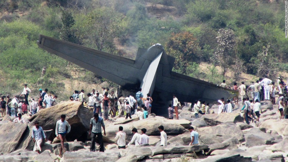 People in the central Indian state of Madhya Pradesh stand next to debris from a plane that crashed Friday, March 28. Five people from the Indian Air Force were killed in the crash, which took part during a routine training mission, authorities said.