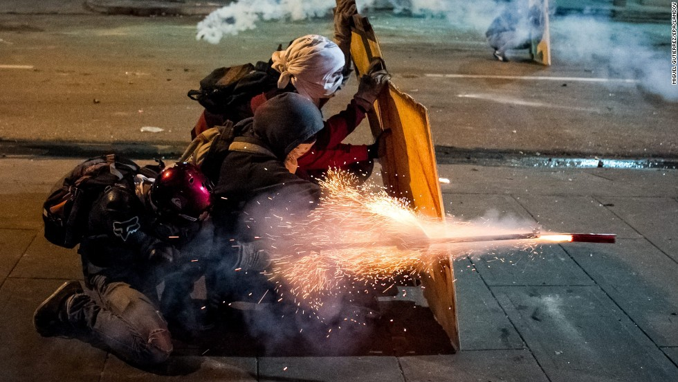 Demonstrators clash with police during an anti-government protest in Caracas, Venezuela, on Sunday, March 30.