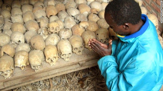 A Rwandan survivor of the 1994 Genocide prays over the bones of genocide victims at a mass grave in Nyamata, Rwanda, in this April 6, 2004 file photo.