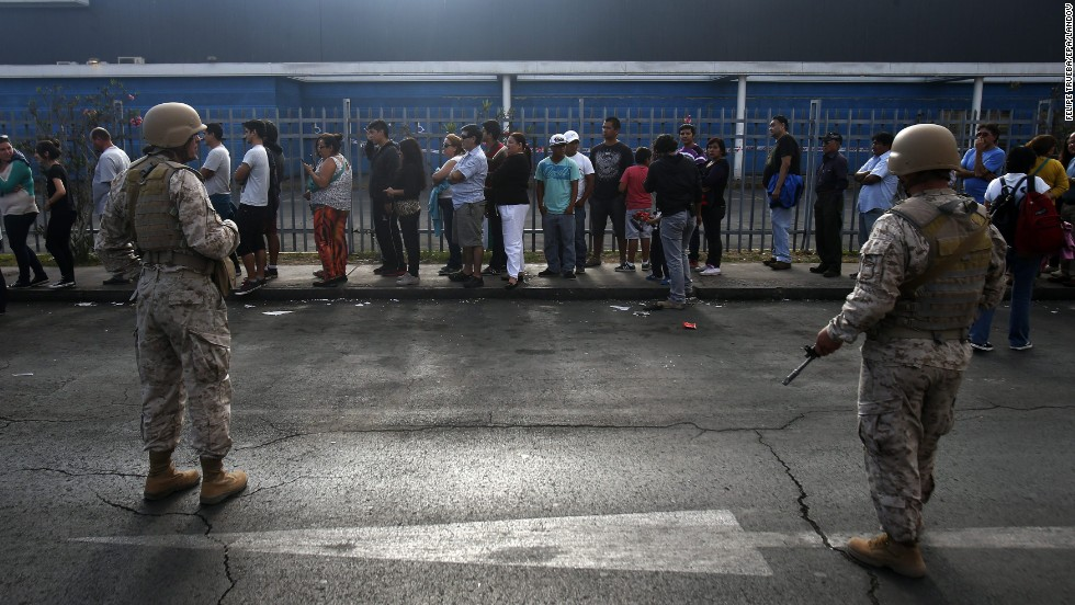 Chilean soldiers stand guard at a supermarket as people wait in line to buy supplies in Iquique, Chile, on April 3.