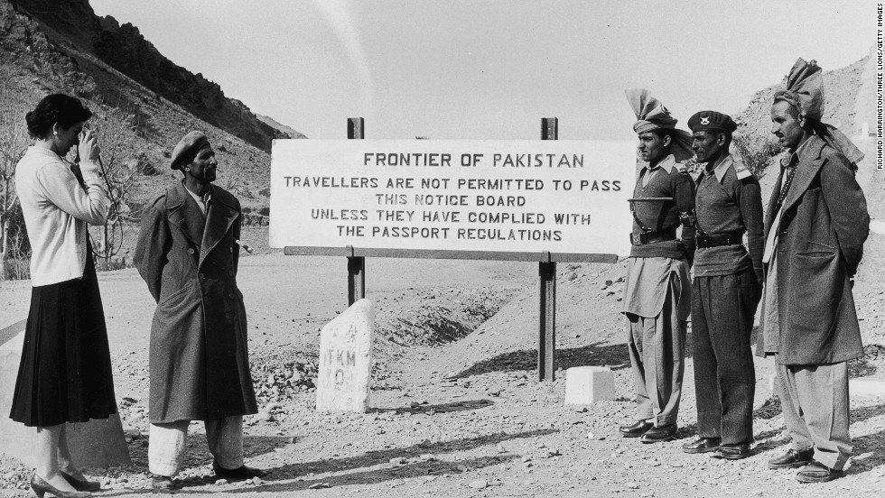 An Afghan woman, dressed in western-style clothing and standing comfortably around men, takes a photograph at the frontier between Pakistan and Afghanistan. This photograph was taken circa 1955.