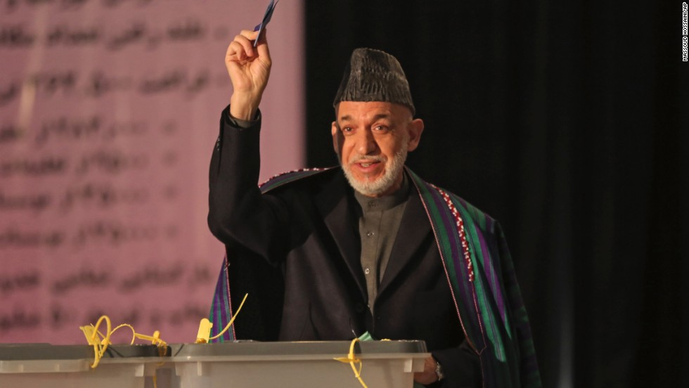 President Hamid Karzai shows his ballot to the media before he casts his vote at Amani High School, near the presidential palace in Kabul.