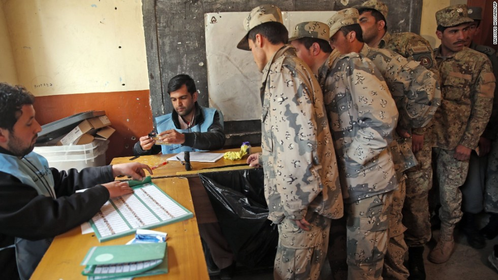 Afghan security personnel line up for registration before voting at a polling station in Kabul.