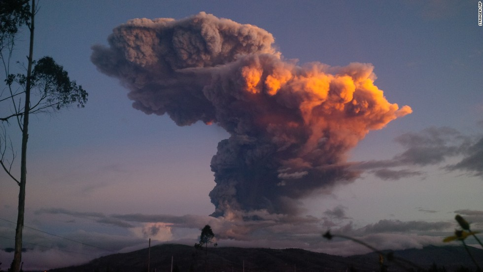 The Tungurahua volcano, as seen from Ambato, Ecuador, spews a column of ash in April 2014. The volcano emitted a 6-mile-high column of ash after a powerful, five-minute explosion that shot pyroclastic material onto its northern and northwestern flanks. The volcano has been active since 1999, with several major eruptions in that span.
