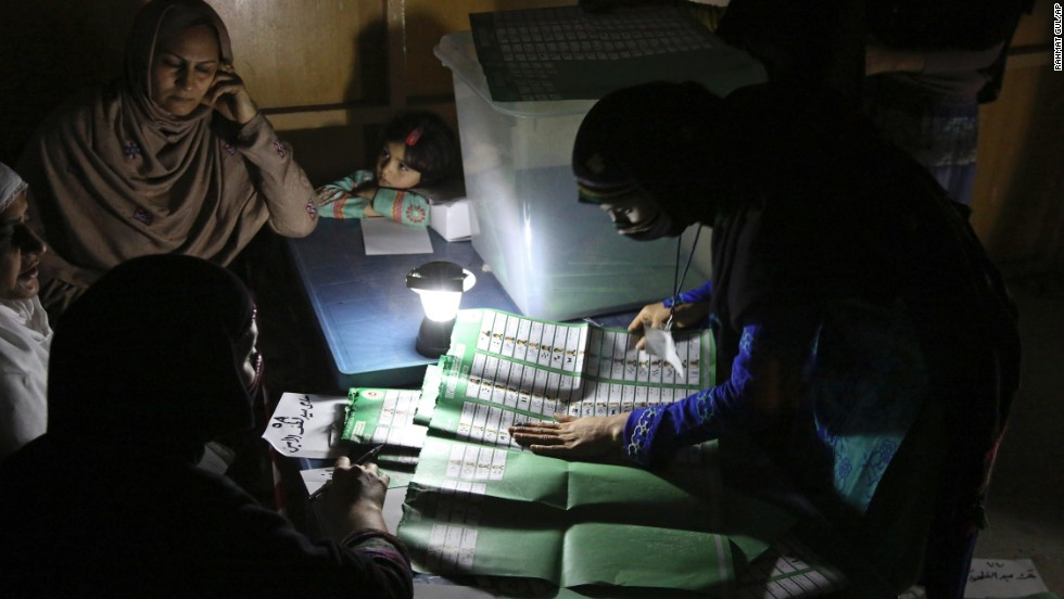 Afghan election workers count ballots by the light of a lantern at a polling station in Jalalabad, Afghanistan, on Saturday, April 5.