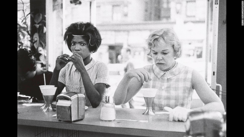 A black woman and a white woman sit next to each other at a New York City restaurant in 1962.