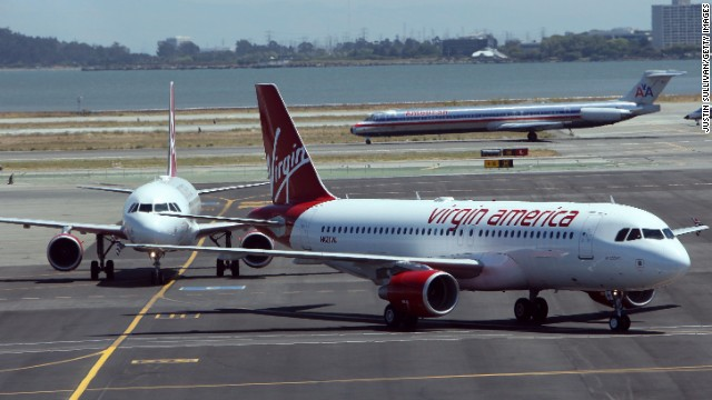 Two Virgin America planes taxi on the runway after arriving at San Francisco International Airport after their first flights from New York and Los Angeles August 8, 2007 in San Francisco, California. San Francisco based Virgin America launched its low-cost airfare that offers flights between New York,  Los Angeles and San Francisco.