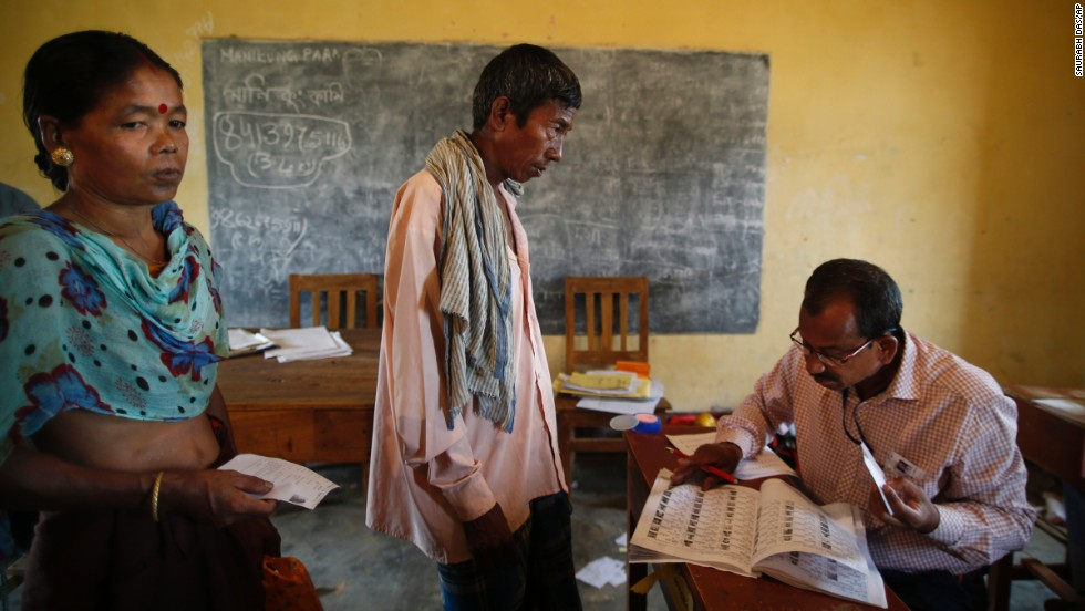 A polling officer in Agartala looks for a voter's name in the registered voter list April 7.