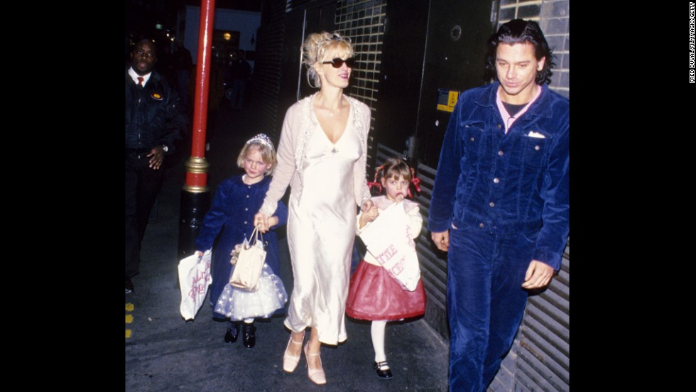 In 1996, Yates walks with Michael Hutchence, of INXS, and her daughters Peaches and Pixie Geldof. The following year, Hutchence was found dead in his hotel room.