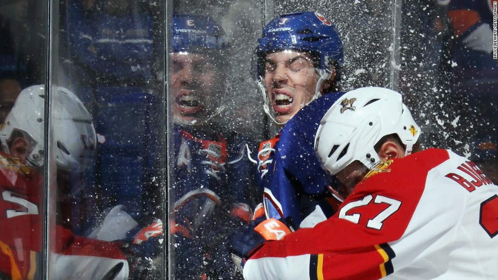 Travis Hamonic of the New York Islanders is checked into the glass by Nick Bjugstad of the Florida Panthers during an NHL game Tuesday, April 1, in Uniondale, New York.