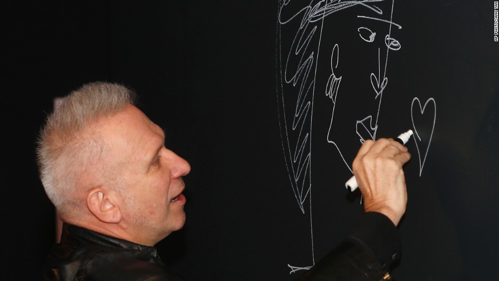 The French couturier Jean Paul Gaultier signs on the wall to launch of his exhibition.
