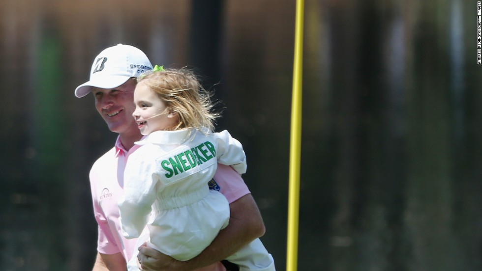 Brandt Snedeker of the United States walks with his daughter Lily around the Augusta course.