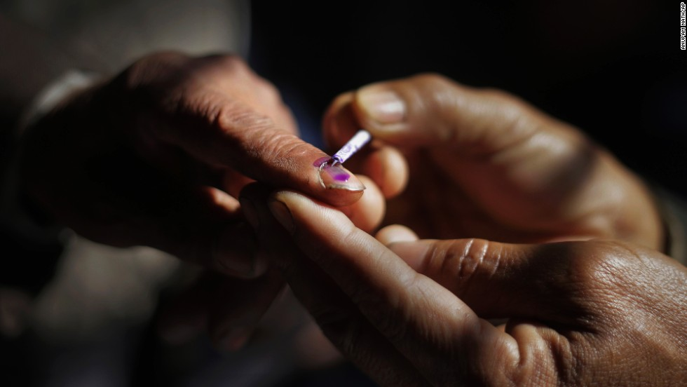 A polling official marks a voter's finger with ink in Senapati on April 9.