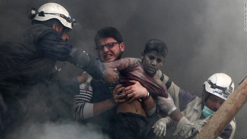 Men in Aleppo, Syria, pull a boy out of rubble Sunday, April 6, after what activists say was a bombing carried out by forces loyal to Syrian President Bashar al-Assad.