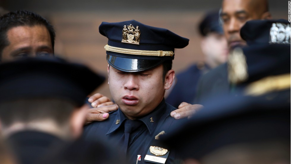 A police officer in New York City is comforted Wednesday, April 9, after a ceremony in honor of Officer Dennis Guerra. Guerra died Wednesday after he and his partner were injured responding to a fire.