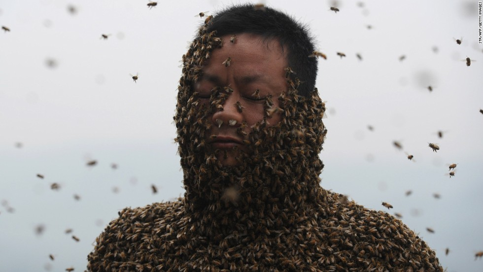 Beekeeper She Ping tries to cover his body with bees Wednesday, April 9, in Chongqing, China.
