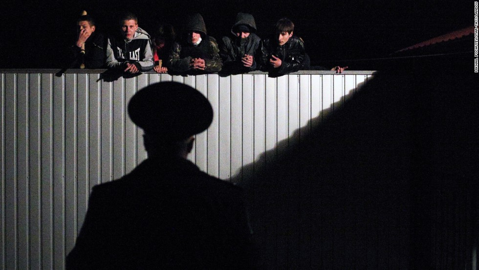 Pro-Russian young men look over the fence of a military recruitment office in Donetsk on Thursday, April 10.