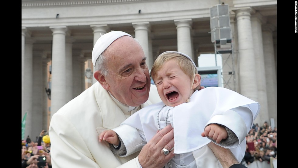 Daniele De Sanctis, a 19-month-old child dressed up as a pope, is handed to Francis as the pontiff is driven through the crowd in St. Peter's Square in February 2014.